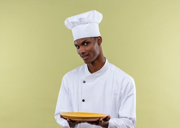 シェフの制服を着た若い驚いたアフリカ系アメリカ人の料理人は、緑の壁に分離された両手で空のプレートを保持します