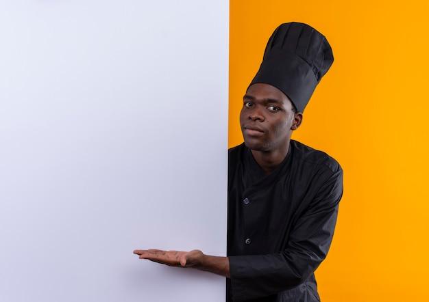シェフの制服を着た若い驚いたアフリカ系アメリカ人の料理人が後ろに立って、コピースペースのあるオレンジ色の白い壁を指しています