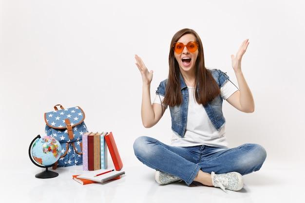 Молодая удивленная изумленная студентка в очках с красным сердцем, раздвигая руки, сидя рядом с земным шаром, рюкзаком, школьными учебниками, изолированными на белой стене