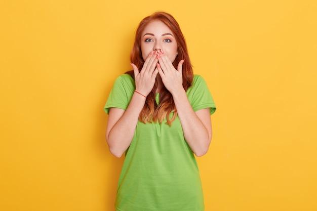 Молодая удивленная, изумленная девушка закрыла рот двумя руками, слышит невероятные новости, красивая женщина с рыжими волосами на желтом фоне.