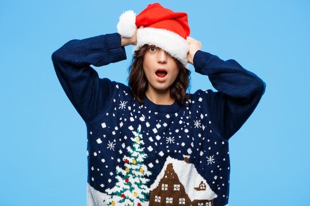 Bella ragazza castana sorpresa giovani in maglione e cappello tricottati di natale sopra la parete blu