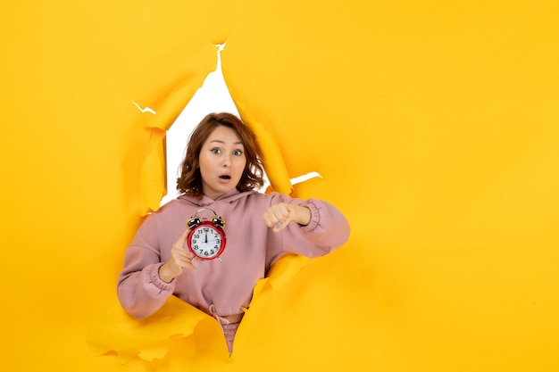 Young surprised beautiful lady holding clock and checking her time on yellow torn breakthrought background