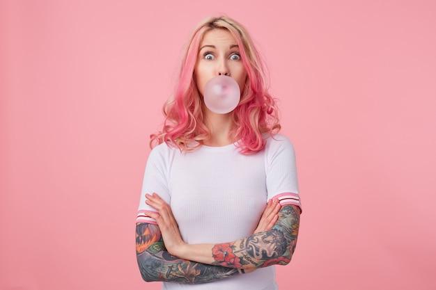 Молодая удивленная красивая розоволосая женщина с татуированными руками, одетая в белую футболку, дует жвачку, удивленно смотрит налево, стоит.