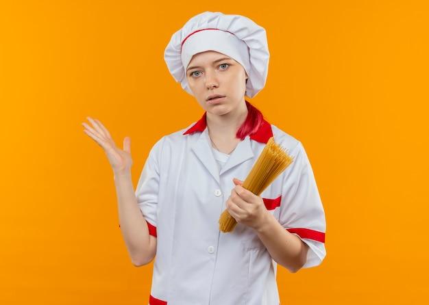 Молодая удивленная блондинка-шеф-повар в форме шеф-повара держит кучу спагетти и указывает в сторону рукой, изолированной на оранжевой стене