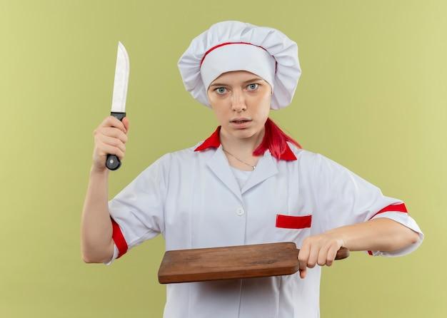 Молодая удивленная блондинка-шеф-повар в форме шеф-повара держит нож и разделочную доску, изолированные на зеленой стене