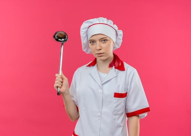 Молодая удивленная блондинка-шеф-повар в форме шеф-повара держит ковш и выглядит изолированной на розовой стене