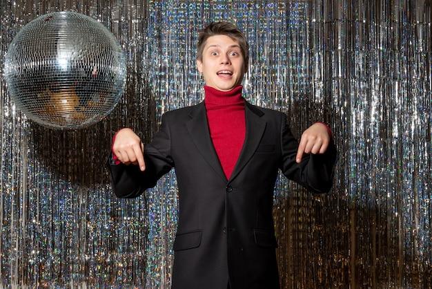 젊은 놀란 금발 남자는 파티에서 아래를 가리키는 정장에 빨간 터틀넥과 청바지를 착용