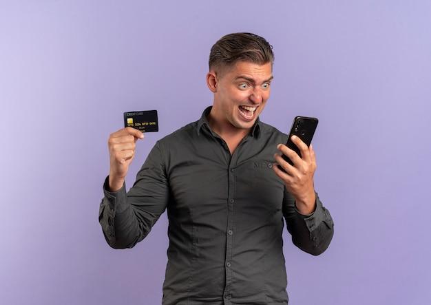 若い驚いた金髪のハンサムな男はクレジットカードを保持し、電話を見て