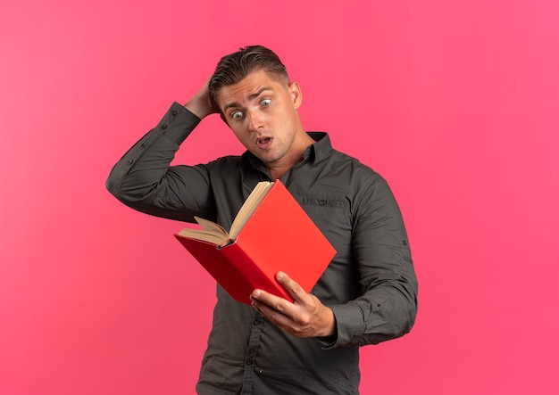 Young surprised blonde handsome man holds head and looks at book isolated on pink background with copy space