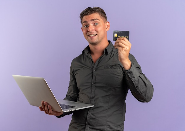 Il giovane uomo bello biondo sorpreso tiene il computer portatile e la carta di credito Foto Gratuite
