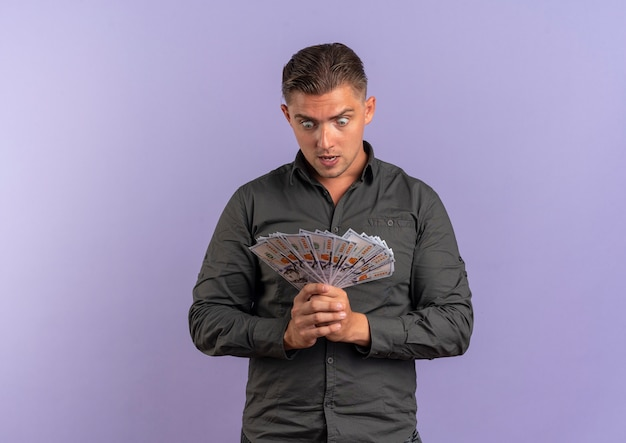 Young surprised blonde handsome man holds and looks at money isolated on violet space with copy space