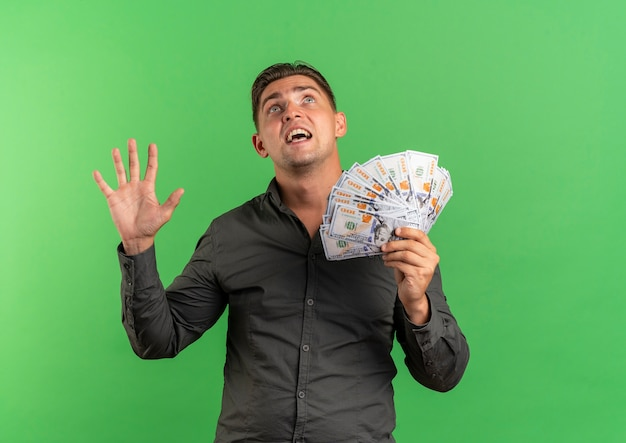 Young surprised blonde handsome man holds money with raised hand looking up isolated on green space with copy space