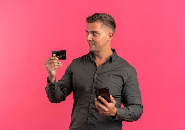 若い驚いた金髪のハンサムな男は電話を保持し、クレジットカードを見て
