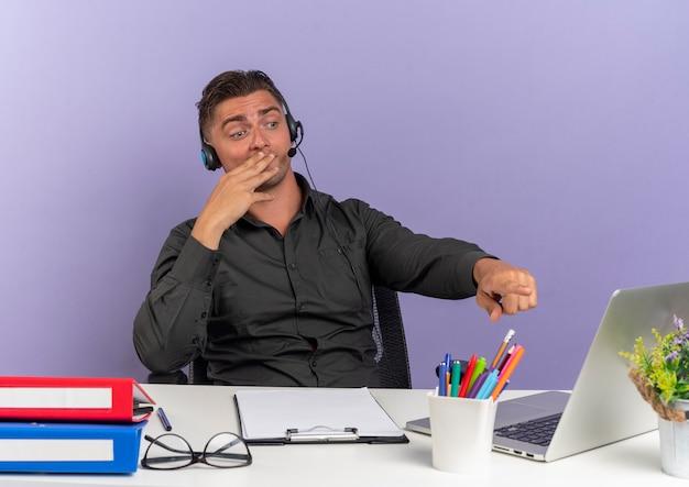 헤드폰에 젊은 놀란 금발 회사원 남자 사무실 도구를보고 노트북을 가리키는 책상에 앉아 복사 공간이 보라색 배경에 고립 된 입에 손을 넣습니다