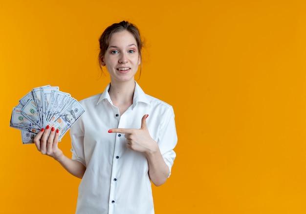 Молодая удивленная русская блондинка держит и указывает на деньги на оранжевом с копией пространства