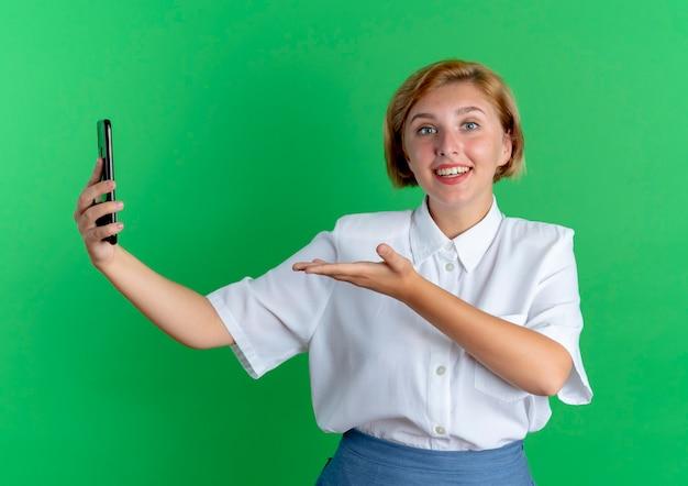 Молодая удивленная русская блондинка держит и указывает рукой на телефон, изолированные на зеленом фоне с копией пространства