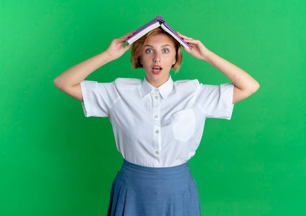 Young surprised blonde russian girl holds book over head isolated on green background with copy space