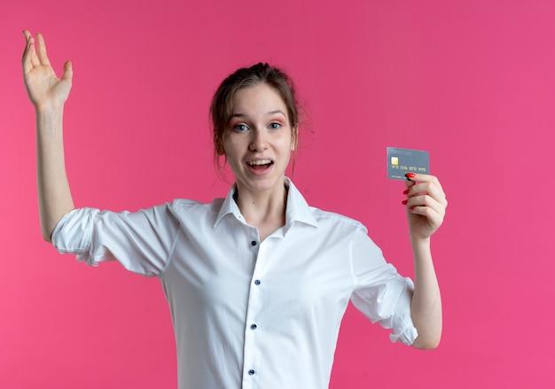 Giovane ragazza russa bionda sorpresa tiene la carta di credito e alza la mano
