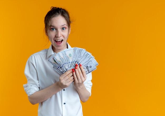 Молодая удивленная русская блондинка держит деньги, изолированные на оранжевом пространстве с копией пространства