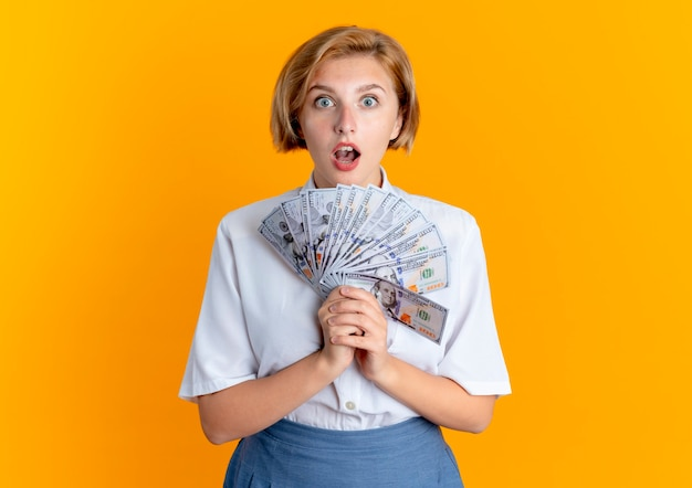 Young surprised blonde russian girl holds money looking at camera isolated on orange background with copy space