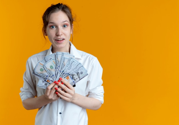 젊은 놀란 금발 러시아 여자 복사 공간 오렌지에 돈을 보유