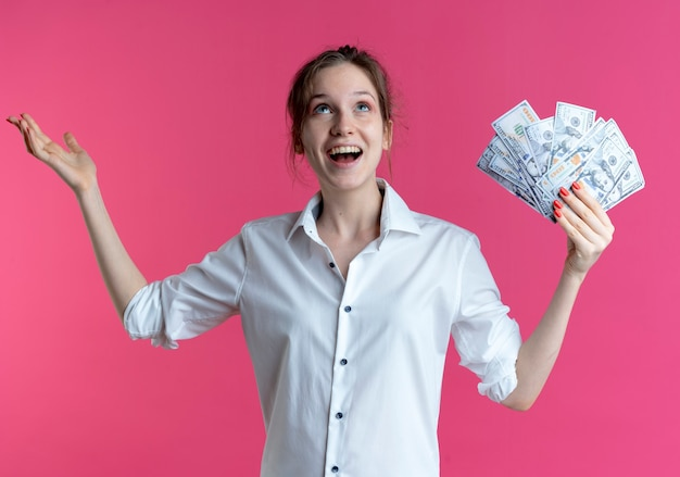 Young surprised blonde russian girl holds money and raises hand looking up on pink  with copy space