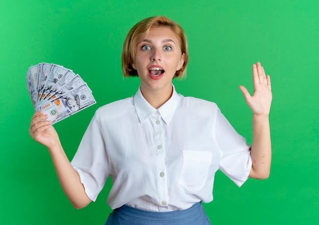 Молодая удивленная русская блондинка держит деньги с поднятой рукой, изолированными на зеленом пространстве с копией пространства