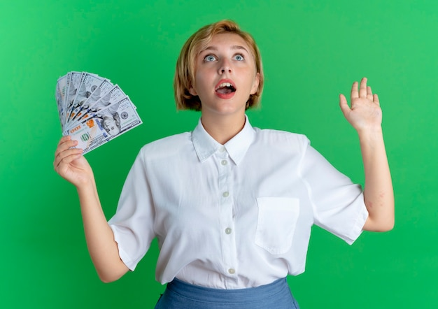 Young surprised blonde russian girl holds money with raised hand looking up isolated on green background with copy space