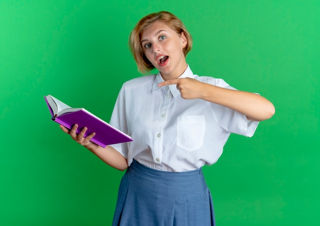 Young surprised blonde russian girl holds and points at book isolated on green background with copy space