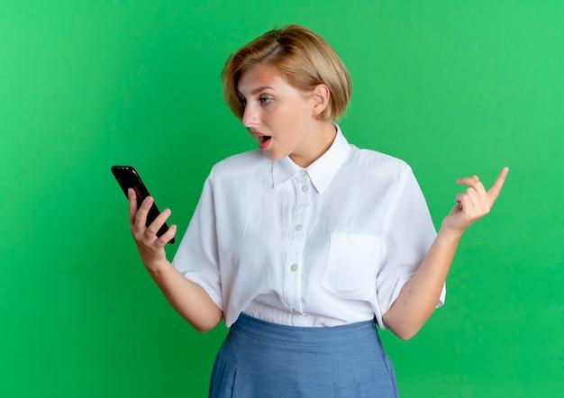 La giovane ragazza russa bionda sorpresa esamina il telefono isolato su priorità bassa verde con lo spazio della copia