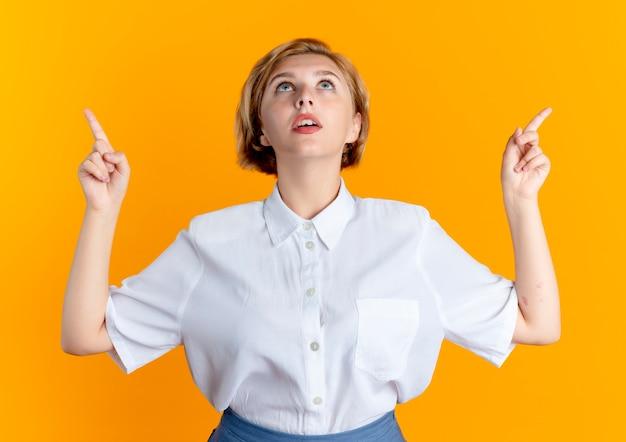 Молодая удивленная русская блондинка показывает пальцем и смотрит вверх