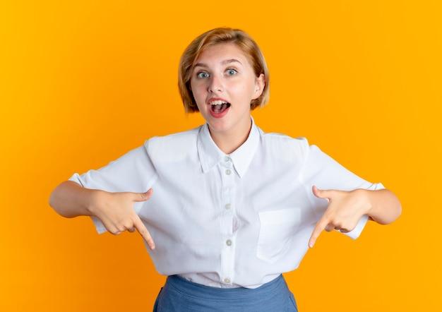 젊은 놀란 금발 러시아 여자 포인트 복사 공간이 오렌지 배경에 고립