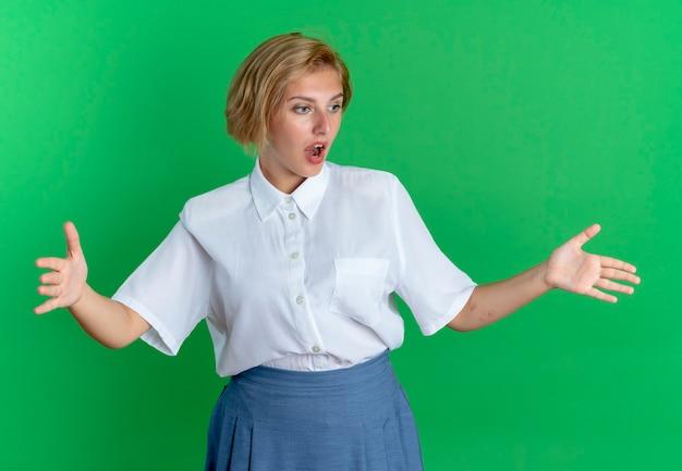 Giovane ragazza russa bionda sorpresa finge di tenere qualcosa e lo guarda isolato su sfondo verde con spazio di copia