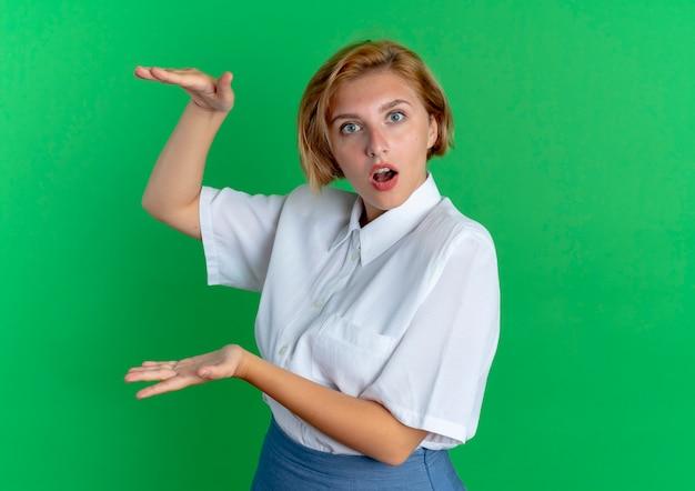 Молодая удивленная русская блондинка делает вид, что что-то держит