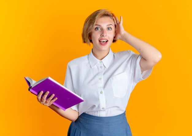 La giovane ragazza russa bionda sorpresa mette la mano sulla testa che tiene il libro