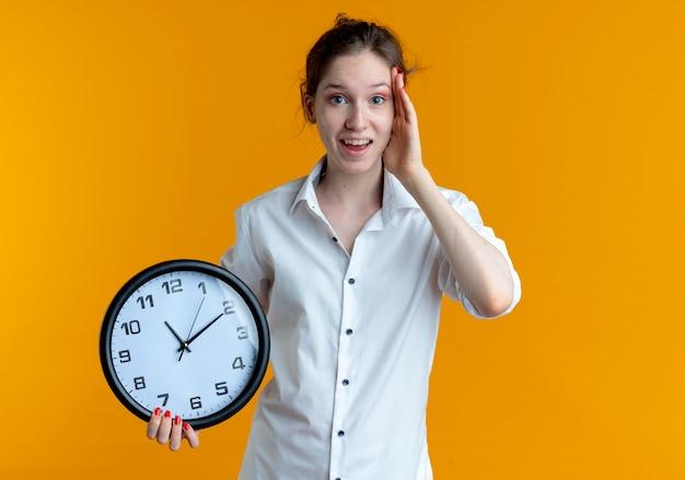 La giovane ragazza russa bionda sorpresa mette la mano sulla testa che tiene l'orologio isolato sullo spazio arancione con lo spazio della copia