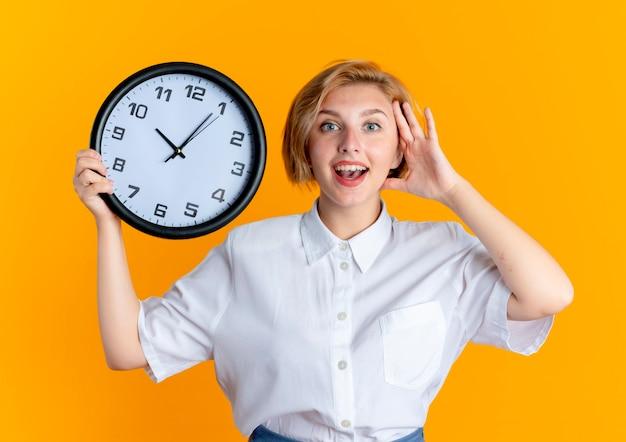 La giovane ragazza russa bionda sorpresa mette la mano sulla testa tiene l'orologio isolato su fondo arancio con lo spazio della copia
