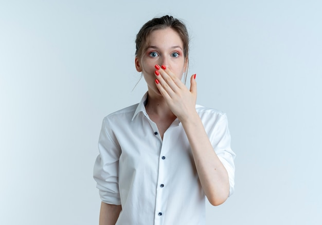Young surprised blonde russian girl puts hand on mouth isolated on white background with copy space