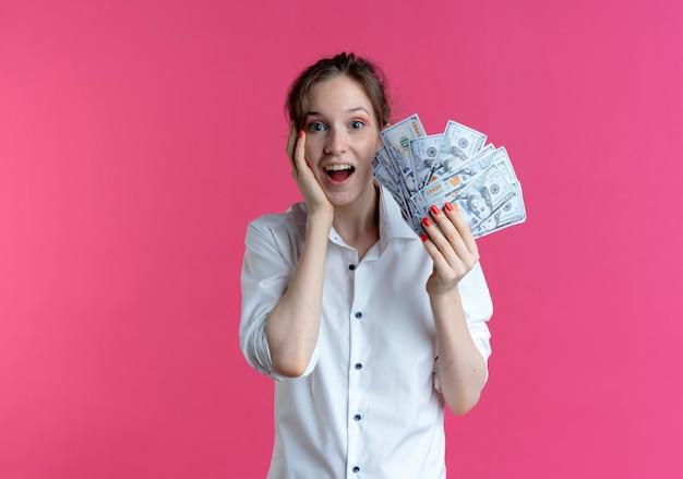 Молодая удивленная русская блондинка кладет руку на лицо, держа деньги на розовом с копией пространства