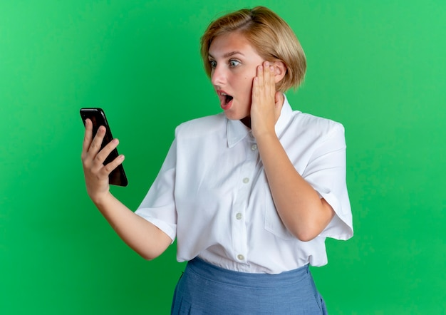 Молодая удивленная русская блондинка кладет руку на лицо, глядя на телефон, изолированные на зеленом фоне с копией пространства
