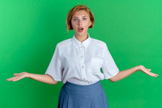 La giovane ragazza russa bionda sorpresa sta con le braccia aperte isolate su priorità bassa verde con lo spazio della copia