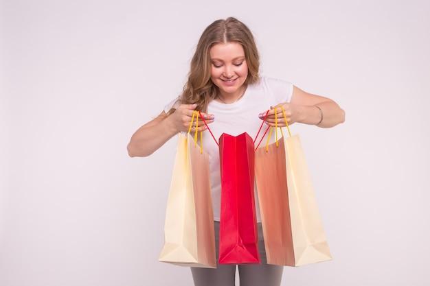 젊은 놀란 금발의 여자는 흰색 쇼핑백에 봐