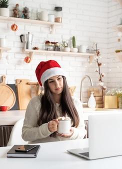 Молодая удивленная брюнетка женщина в шляпе санты болтает с друзьями, используя свой ноутбук