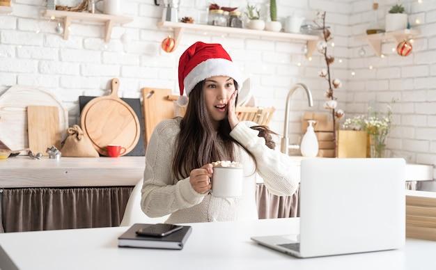 彼女のラップトップを使用して友達とチャットサンタ帽子の若い驚いたブルネットの女性
