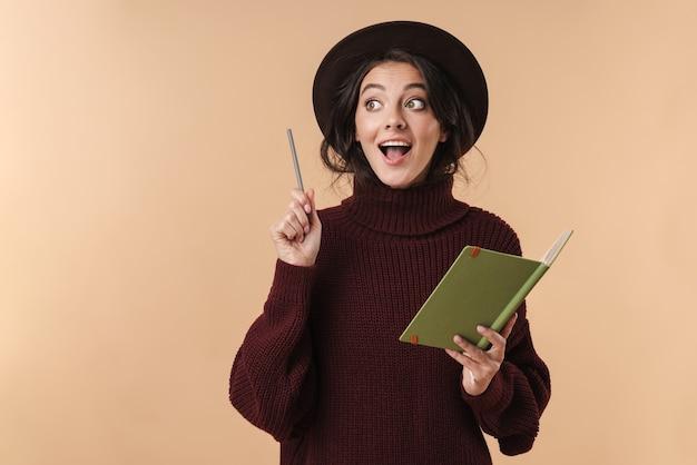 Молодая удивленная брюнетка женщина, изолированных на бежевой стене, написание заметок в записной книжке, имеет идею.