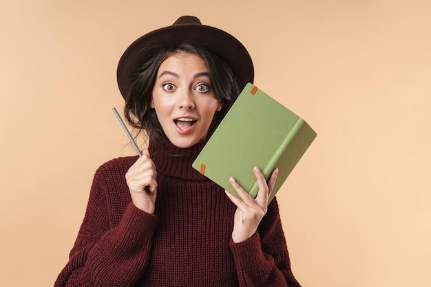Молодая удивленная брюнетка женщина, изолированных на бежевой стене, написание заметок в записной книжке.
