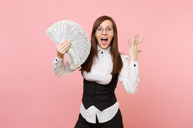 Young surprised business woman in glasses holding bundle lots of dollars, cash money spreading hands isolated on pink background. lady boss. achievement career wealth. copy space for advertisement.