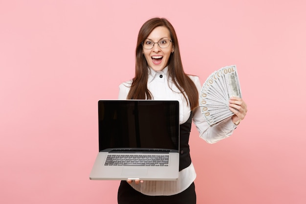 Young surprised business woman holding bundle lots of dollars, cash money and laptop pc computer with blank empty screen isolated on pink background. lady boss. achievement career wealth. copy space.