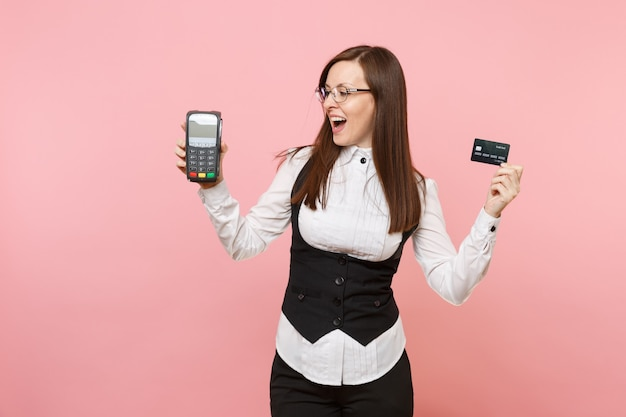 Young surprised business woman holding wireless modern bank payment terminal to process and acquire credit card payments, black card isolated on pink background. lady boss. achievement career wealth.