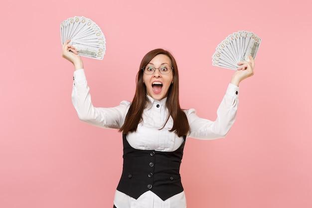 Молодой удивлен бизнес-леди в очках, держа пачку много долларов, раздвигая руки наличными деньгами, изолированными на розовом фоне. леди босс. достижение карьерного богатства. скопируйте место для рекламы.